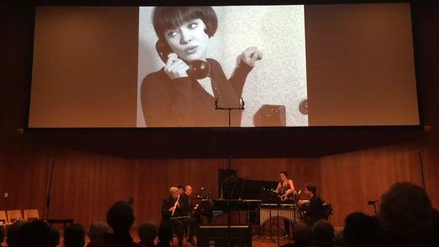 Quartet playing below large screen showing BW vintage movie.